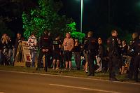 """Nach den pogromartigen Ausschreitungen gegen eine Fluechtlinsunterkunft im saechschen Heidenau am Freitag den 21. August 2015 durch Anwohnerinnen der Ortschaft, kamen am Samstag de 22. August 2015 ca. 250 Menschen in die Ortschaft um ihre Solidaritaet mit den Gefluechteten zu zeigen.<br /> Am Vorabend hatten Rassisten, Nazis und Hooligans sich zum Teil Strassenschlachten mit der Polizei geliefert um zu verhindern, dass Fluechtlinge in einen umgebauten Baumarkt einziehen. Ueber 30 Polizisten wurden dabei verletzt.<br /> Bis in die Abendstunden des 22. August blieb es trotz spuerbarer Anspannung um die Unterkunft ruhig. Im Laufe des Tages wurden immer wieder Gefluechtete mit Reisebussen gebracht was von den wartenenden Heidenauern mit Buh-Rufen begleitet wurde. Vereinzelt wurde auch """"Sieg Heil"""" gerufen, was die Polizei jedoch nicht verfolgte.<br /> Kurz vor 23 Uhr griffen Nazis und Hooligans wie am Vorabend die Polizei mit Steinen, Flaschen, Feuerwerkskoerpern und Baustellenmaterial an. Die Polizei mussten mehrfach den Rueckzug antreten, scheuchte den Mob dann von der Fluechtlingsunterkunft weg. Dabei wurden auch wieder Traenengasgranaten verschossen. Mindestens ein Nazi wurde festgenommen.<br /> Im Bild: Polizeibeamte fordern die Rechten auf die Fahrbahn frei zu halten.<br /> 22.8.2015, Heidenau/Sachsen<br /> Copyright: Christian-Ditsch.de<br /> [Inhaltsveraendernde Manipulation des Fotos nur nach ausdruecklicher Genehmigung des Fotografen. Vereinbarungen ueber Abtretung von Persoenlichkeitsrechten/Model Release der abgebildeten Person/Personen liegen nicht vor. NO MODEL RELEASE! Nur fuer Redaktionelle Zwecke. Don't publish without copyright Christian-Ditsch.de, Veroeffentlichung nur mit Fotografennennung, sowie gegen Honorar, MwSt. und Beleg. Konto: I N G - D i B a, IBAN DE58500105175400192269, BIC INGDDEFFXXX, Kontakt: post@christian-ditsch.de<br /> Bei der Bearbeitung der Dateiinformationen darf die Urheberkennzeichnung in den EXIF- und  IPTC-Daten nicht entfernt """