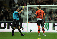 Pictured: Clint Hill of QPR (R) sees a yellow card by match referee Lee Probert (L). Tuesday 27 December 2011<br />