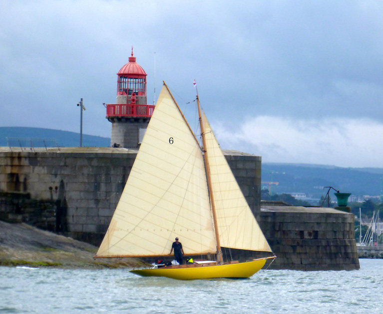 Home again. After an absence of 35 years - and all of 116 years after she first sailed here - the restored Dublin Bay 21 Naneen sails past Dun Laoghaire's East Pier lighthouse with a 21-gun salute