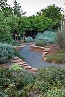 Gravel path winding between flagstone garden walls toward shaed vine covered ramada in backyard New Mexico garden, design by Judith Phillips