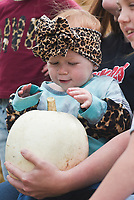 Hannah Montgomery, 1, of Bentonville reacts at a pumpkin, Thursday, October 15, 2020 at the Benton County Fairgrounds in Bentonville. The 4th annual Fall Y'all Craft Fair featured 40 vendors, half capacity to previous years, as well as local food trucks, photo opportunities and a pumpkin patch. The fair ends on Sunday. Check out nwaonline.com/2010013Daily/ for today's photo gallery. <br /> (NWA Democrat-Gazette/Charlie Kaijo)