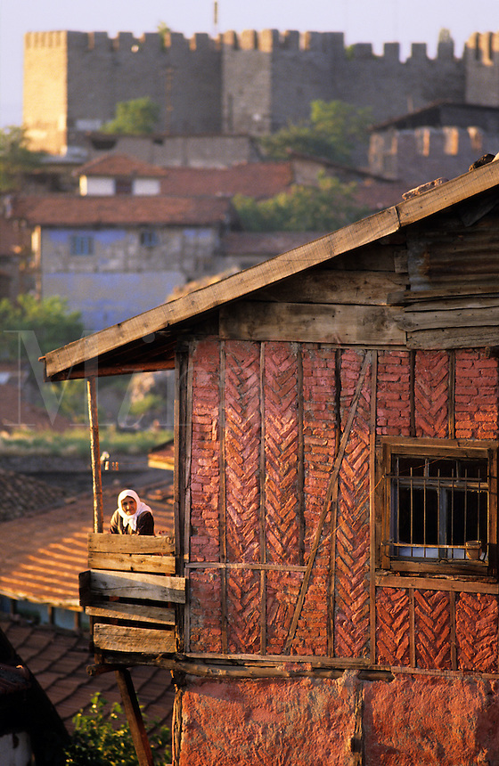 Turkey. Ankara. Old town. Woman watching from balcony and the Citadel in the background..