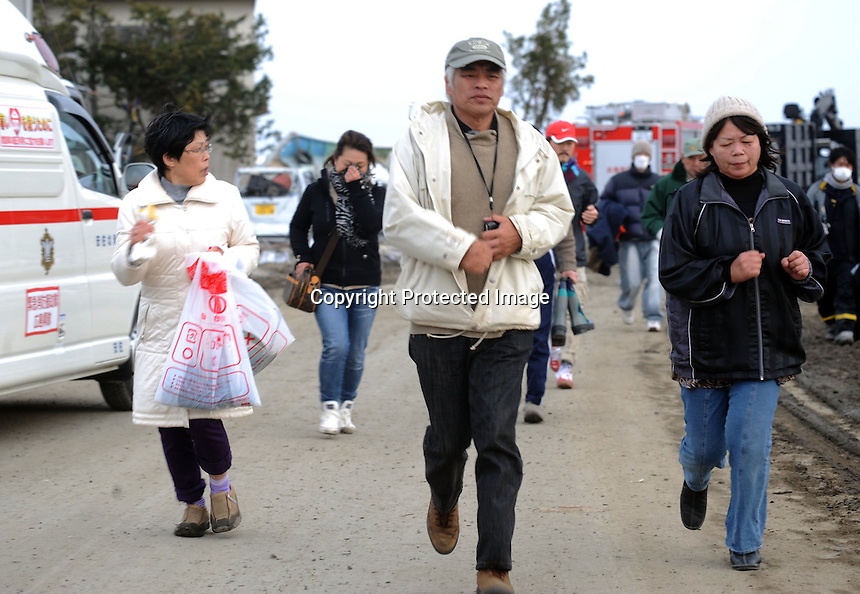 People run away from the coast after a Tsunami warning alert in the  town of Natori, after the Tsunami devastated the entire pacifc coastline of Japan after the earthquake and tsunami devastated the area Sendai, Japan.<br /> <br /> photo by Richard Jones/ sinopix
