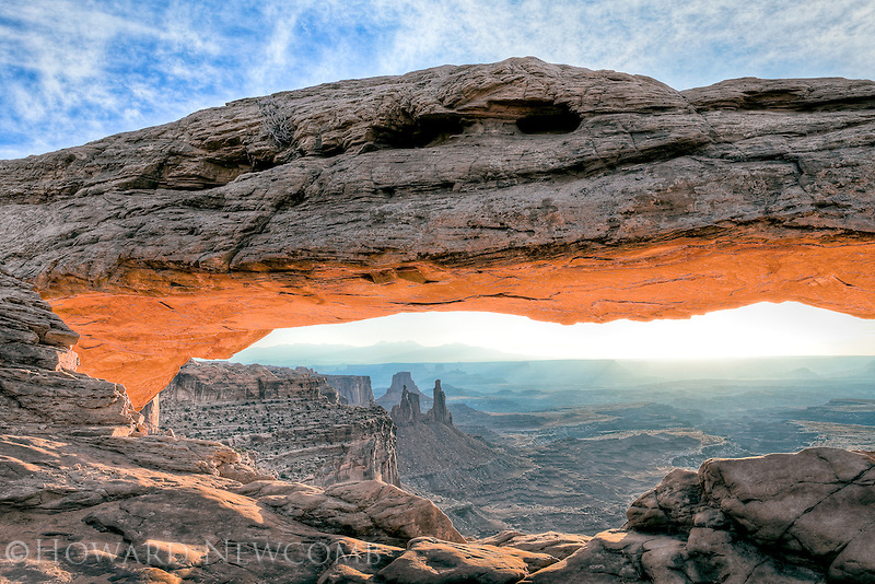 Iconic Mesa Arch glows from the reflected sunrise light off of the surronding red rocks.  Located in the Island in the Sky district of Canyonlands National Park, Utah.