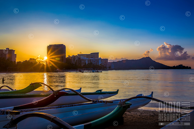 The sun rises over Waikiki, with outrigger canoes in the foreground; in the distance, a man stands in the shallows on the left and Diamond Head is further out on the right, Honolulu, O'ahu.