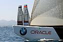 Louis Vuitton Trophy La Maddalena 22 maggio 2010. E' il primo giorno di regate. Dietro la prua di uno degli scafi BMW Oracle spuntano le vele di Aleph e Team Origin che si preparano a partire
