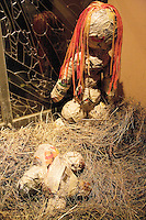 """Switzerland. Canton Tessin. Vira Gambarogno. The old town shows an exhibit of various Nativity scenes, illuminated at night for the Christmas holiday season. A Nativity Scene, may be used to describe any depiction of the Nativity of Jesus in art, but in the sense covered here, also called a crib or in North America and France a crèche (meaning """"crib"""" or """"manger"""" in French). It means a three-dimensional folk art depiction of the birth or birthplace of Jesus, either sculpted or using two-dimensional (cut-out) figures arranged in a three-dimensional setting. Christian nativity scenes, in two dimensions (drawings, paintings, icons, etc.) or three (sculpture or other three-dimensional crafts), usually show Jesus in a manger, Joseph and Mary in a barn (or cave). Sculture of the Vigin Mary and Jesus. © 2007 Didier Ruef"""