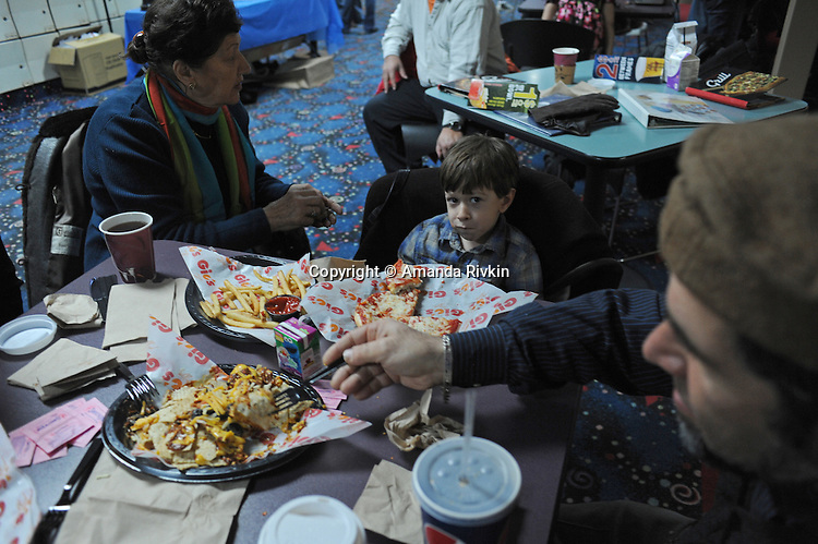 Najiba Babar, great-grandson Omid Gish, 4, and uncle Daud Babar, all Kabul-born Afghan-American immigrants except American-born Gish, snack on nachos, french fries, and pizza during the lunch hour at the Afghan Bowling Tournament in Annandale, Virginia on February 28, 2010.