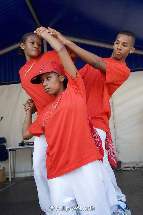 Teenagers from the Fourth Feathers Youth Club give a dance performance at Church Street Summer Festival 2005, Paddington, London.