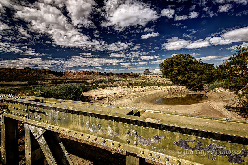 A steel bridge over a wash in the Rio Puerco Valley with Cabezon Peak in the distance.