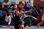Children run ahead of a model bull used to train bullfighters after the first bull run of the San Sebastian de los Reyes Festival near Madrid, on August 26, 2014. © Pedro ARMESTRE