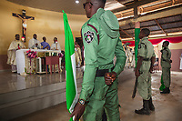 """Nigeria. Abakaliki State. Uburu Amach. St. Patrick's Catholic Church. Three Igbo men in green uniform from the Organization """"Man of Order and Discipline Movement of Nigeria (M.O.D)"""" during the mass celebration for the 25th Priesthood Anniversary of Reverend Father Edward Inyanwachi. The Organization """"Man of Order and Discipline Movement of Nigeria (M.O.D)"""" is a Catholic voluntary organization. It was founded in the year 1983 by a Priest of the Catholic Church Most Rev. Monsignor Patrick O. Achebe. 14.07.19 © 2019 Didier Ruef"""