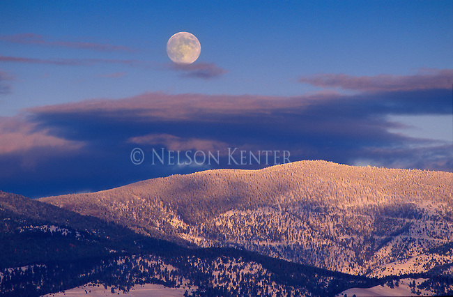 The full moon rises over snow covered hills above Missoula, Montana