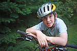 Nine year old boy leaning on the handlebars of his mountain bike.