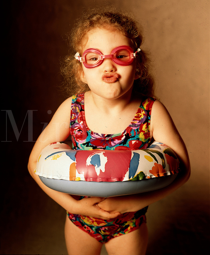 A 5 year old girl in swimsuit making fish face with goggles and inner tube. Birmingham AL USA studio.