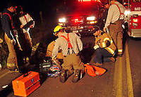 Occidental Volunter Fire Department and paramedics treat the victim of a motorcycle accident as the bike rests in a ditch. Occidental, California