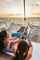 Two women enjoy the sunset view from a catamaran cruise along the Kona coast of Hawai'i Island.