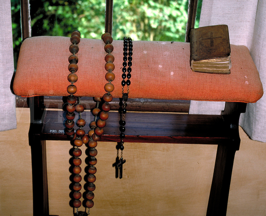 Old, oversized, Catholic Rosary prayer beads are placed on a bench next to a Bible or prayer book. Displayed in the Rural Life Museum of Lafayette, Louisiana. Lafayette Louisiana, Rural Life Museum.