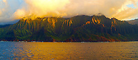Golden sunset light skims across the rugged cliffs of Na Pali, Kauai, along the eleven mile Kalalau Trail.