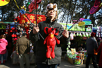 CHINA. A man selling toys during Chinese New Year in Ditan Park in Beijing.  Chinese New Year, or Spring Festival, is the most important festival and holiday in the Chinese calendar In mainland China, many people use this holiday to visit family and friends and also visit local temples to offer prayers to their ancestors. The roots of Chinese New Year lie in combined influences from Buddhism, Taoism, Confucianism, and folk religions.  2008