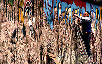 BERLINO / GERMANIA - 20 NOVEMBRE 1989.UN ANZIANO DI ORIGINE TURCA STACCA PEZZI DI MURO PER VENDERLI COME GADGETS (1 PEZZO=1 DM)..FOTO LIVIO SENIGALLIESI..BERLIN / GERMANY - 20 NOVEMBER 1989.AN OLD MAN TAKING PIECES OF WALL TO SELL AS GADGETS TO THE TURISTS (1 PIECE=1 DM)..PHOTO BY LIVIO SENIGALLIESI