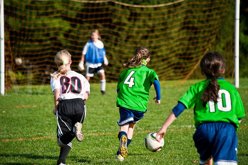 Youth soccer girl dribbles soccer ball to the goal.