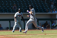 Salt River Rafters first baseman Tyler Nevin (2), of the Colorado Rockies organization, hustles towards home plate in front of manager Tommy Watkins (8) during an Arizona Fall League game against the Mesa Solar Sox at Sloan Park on October 30, 2018 in Mesa, Arizona. Salt River defeated Mesa 14-4 . (Zachary Lucy/Four Seam Images)