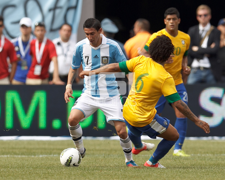 Argentina midfielder Angel Di Maria (7) avoids Brazil defender Marcelo (6) and brings the ball forward. In an international friendly (Clash of Titans), Argentina defeated Brazil, 4-3, at MetLife Stadium on June 9, 2012.