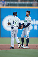 Travis Demeritte (12) of the Gwinnett Stripers brings Cristian Pache (15) his cap and glove between innings of the game against the Charlotte Knights at Truist Field on July 17, 2021 in Charlotte, North Carolina. (Brian Westerholt/Four Seam Images)