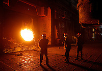 Workers stand next to a steel smelter at Ma Steel (Maanshan Iron & Steel Co.) in Maanshan, Anhui Province, China..10 Apr 2006