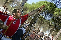 A man stretches to attach the bull's tail onto a lance after the 'El toro de la Vega' (The bull of the plain) bullfight, 13 September 2005 in Tordesillas. On the second Tuesday of September, since the fifteenth century the village has celebrated this very special bullfight. The arena of the bullfight is the plain across the river from the village and it is up to a number of young men with lances to dispute the honour of making the fatal strike. (c) Pedro ARMESTRE
