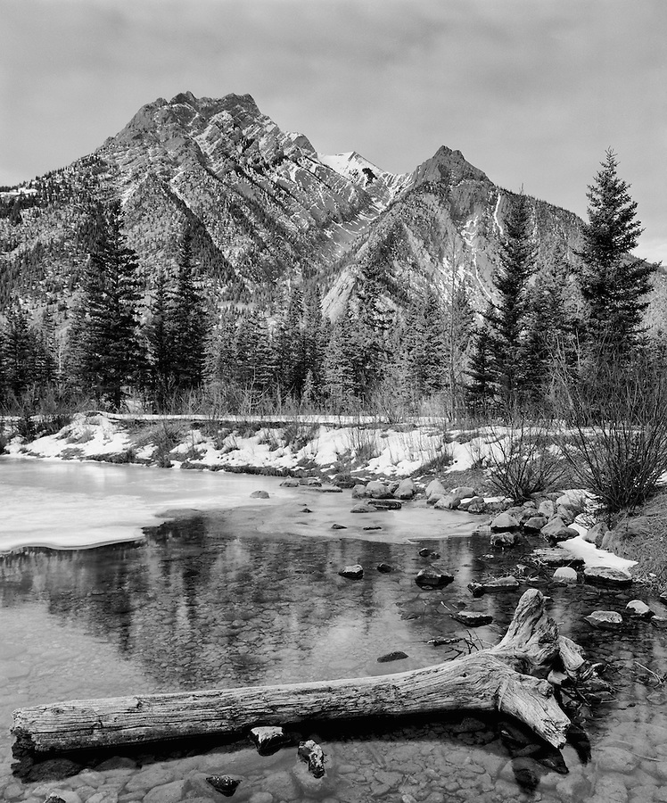 The reflection of Mount Lorette is seen in a partially frozen pond in the Kananaskis Country region of Alberta Canada.