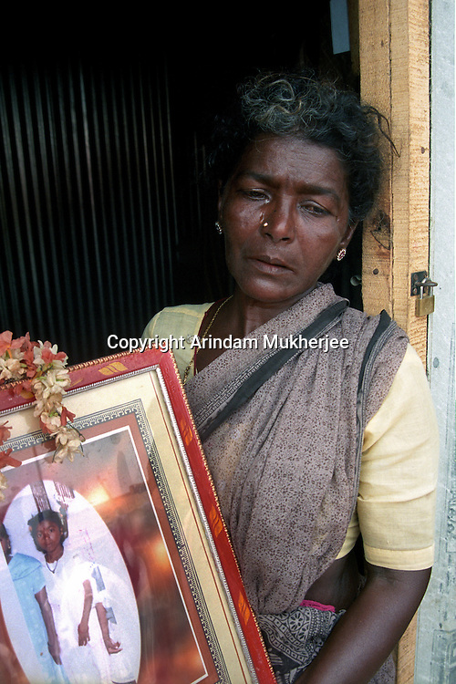 A grieving lady, all that remains is a photograph and the memory of her granddaughter in a Temporary shelter.Nagapattinam.India.
