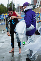 10 AUG 2014 - LIVERPOOL, GBR - Shadow Secretary of State for Health Andy Burnham from Team Liverpool MPs relay team takes off his wetsuit at the end of his swim as he races to tag his team mate, former Liverpool mayor Steve Rotherham, in transition at the Tri Liverpool triathlon in Kings Dock, Liverpool, Great Britain (PHOTO COPYRIGHT © 2014 NIGEL FARROW, ALL RIGHTS RESERVED)
