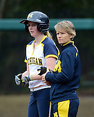 Michigan Wolverines utility player Kelsey Susalla (7) on first base with coach Bonnie Tholl during the season opener against the Florida Gators on February 8, 2014 at the USF Softball Stadium in Tampa, Florida.  Florida defeated Michigan 9-4 in extra innings.  (Copyright Mike Janes Photography)