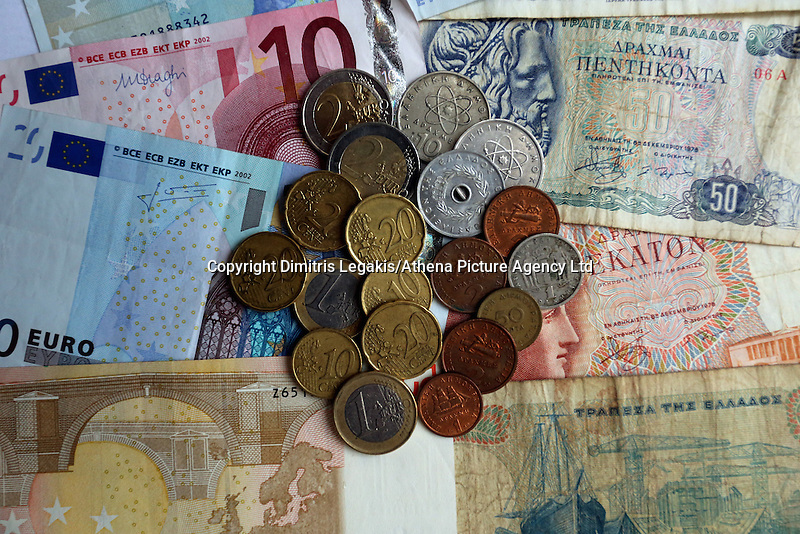 A mixture of old drachma coins and notes along with euros