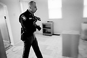 Cleveland, Ohio.March 26, 2008 ..Delivering warning and final eviction notices Detective Robert Kole of the Cuyahoga County Sheriff's Department enters every situation with caution. When the residents are at the home he must assure that all is final and that the home is clear of weapons and that the residents are indeed moving out. ..If no one is there, then he must authorize that the door be forcibly open. He then enters and clears the house at gunpoint in hopes that there are no squatters or inhabitants threaten himself or the movers. He also clears the house for weapons...All emotions and fears are on the surface as some residents greet him by crying on his shoulder while others can threaten him with a weapon..
