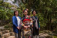 "Japan, Okayama Prefecture, Kurashiki. Woman dresssed in colorful kimono in Tsuru gata yama park. Celebrating Coming of Age Day, ""Seijin no hi,"" the day of turning 20."