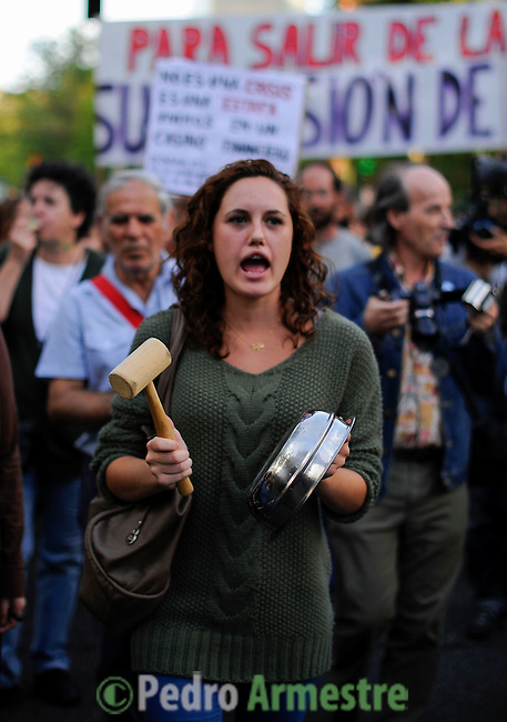 """A woman makes noise with a casserole and a wooden hammer as she takes part in a """"casserole march"""" against government's austerity reforms and the public payment of bank's debts on October 13, 2012 in Madrid. © Pedro ARMESTRE"""