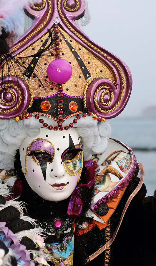 Woman dressed in traditional mask and costume for Venice Carnival standing on Venice waterfront in Piazza San Marco, Venice, Veneto, Italy