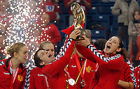 BELGRADE, SERBIA - DECEMBER 16: Milena Knezevic (R) and Ana Dokic (L) of Montenegro lift a trophy during the Women's European Handball Championship 2012 medal ceremony at Arena Hall on December 16, 2012 in Belgrade, Serbia. (Photo by Srdjan Stevanovic/Getty Images)