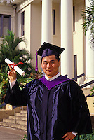 Young man proudly displaying his diploma at college graduation from the University of Hawaii