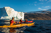 Greenland, Kajser Franz Josef Fjord, Blomsterbukta. Passengers from the FRAM Hurtiguten cruise ship kayaking among ice.