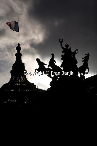 The sculpture Quadriga is seen in dramatic silloutte with a dome of the Grand Palais in Paris France. the French flag is framed by dramatic clouds