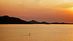 Early Morning Over Port Shelter, Hong Kong.  A Man Gently Paddles A Surf Board For His Morning Exercise.