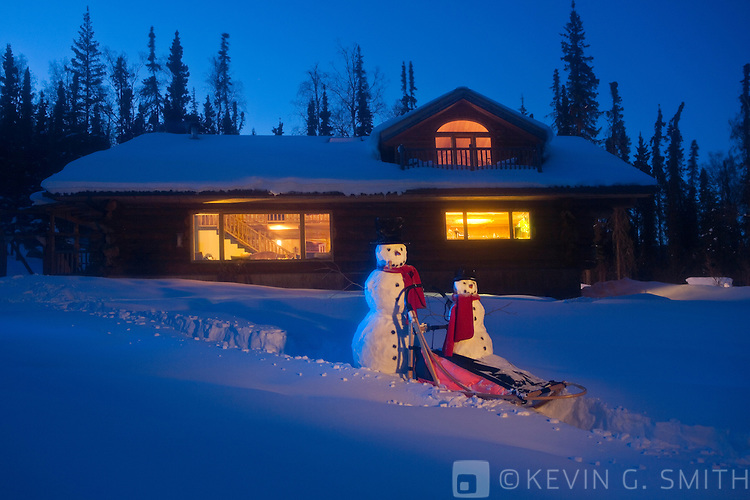 A big and little snowman riding on a dog mushing sled in front of a log cabin style home. Twilight, glowing lights, Fairbanks, Alaska, USA. PR