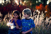 MR / Schenectady, NY. Steinmetz Park (public urban park). Cousins (7) look at milkweed pods in fall. Girl: Columbian American. Book original from Berry Smudges and Leaf Prints. MR: She5, Sen3. © Ellen B. Senisi