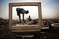 Children break apart CRT (cathode ray tube) monitors to salvage metal from inside at Agbogbloshie dump, which has become a dumping ground for computers and electronic waste from all over the developed world. Hundreds of tons of e-waste end up here every month. It is broken apart, and those components that can be sold on, are salvaged.