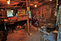 The inside of one side of an early 20th century or late 19th century blacksmiths shop used at a saw mill to make and repair tools in Occidental California.  It shows the working area where the metal was heated with coal.