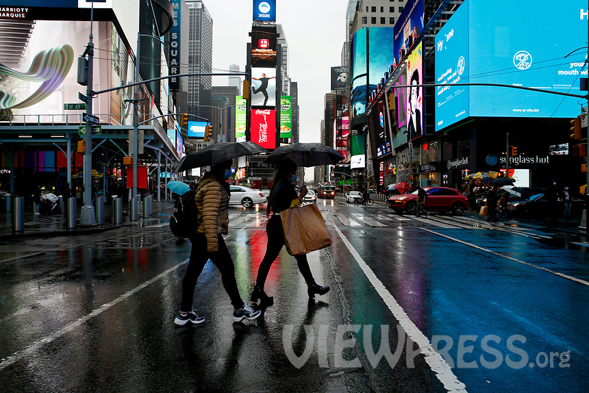 NEW YORK - NEW YORK - MARCH 24: Women cross a street at Times Square on March 24, 2021 in New York. With more people every day getting vaccinated transmission rates are dropping, arts an entertainment values should open at 33% capacity on April 2, as outdoor amusement parks will open at 25% capacity one week later (Photo by John Smith/VIEWpress)